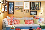 Grass-cloth-covered walls hung with art and a blue couch in a family space