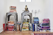 Rainbow colored books stacked on the floor and on top of steel stools.