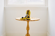 A gold side table displaying a pair of yellow shoes