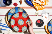 Patterned plates and a striped tablecloth make for a perfect poker surface