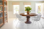 Wire chairs around big natural wood table in window lit dining area.