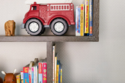 Kids toys on a brown stained wood shelf.