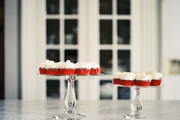 A pair of cake stands topped with red velvet cupcakes