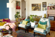 A multi colored space with lots of wall decorations, two chairs, and a sofa.