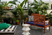 An outdoor cushion, garden stools, an outdoor rug, tropical plants, and a Lars Bolander tête-à-tête on Irene Edwards's roof