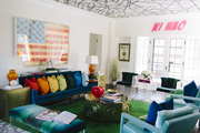A colorful living room with cheeky artwork.