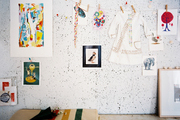 A clothesline of art against a painted corkboard