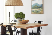 A dining space with black dining chairs and a woven pendant light.