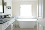 A freestanding tub and penny-tile floors in a bathroom