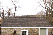 Floral designer Brittany Asch beside a stone-walled outbuilding
