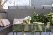 This outdoor space has a green dining set and pink pillows.