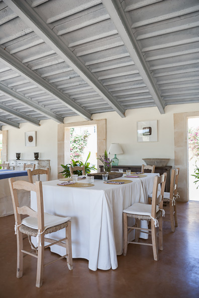 Exposed Beams - Wood chairs around a dining table in a Majorca pool house