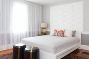 A transitional bedroom with white headboard.