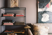 A bookshelf beside a beige couch and a floor lamp