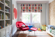 A red womb chair and a striped rug in a child's bedroom