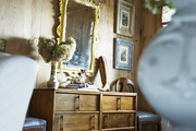 An ornate mirror above an entryway console.