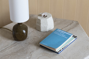 A marble stone side table with reading books and a ceramic lamp.