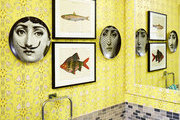 A series of prints in a yellow wallpapered bathroom