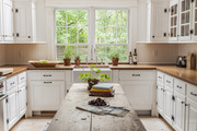 A kitchen with wooden countertop and white built-in cabinets