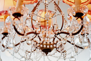 A beaded chandelier with shades trimmed with red pompom fringe