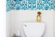 A small bathroom with blue and white wallpaper.
