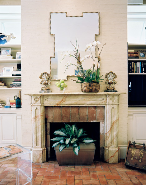 Fireplace - Brick flooring and a faux-marble mantel in a family room