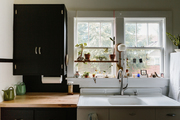 A contemporary kitchen with black and white cabinets.