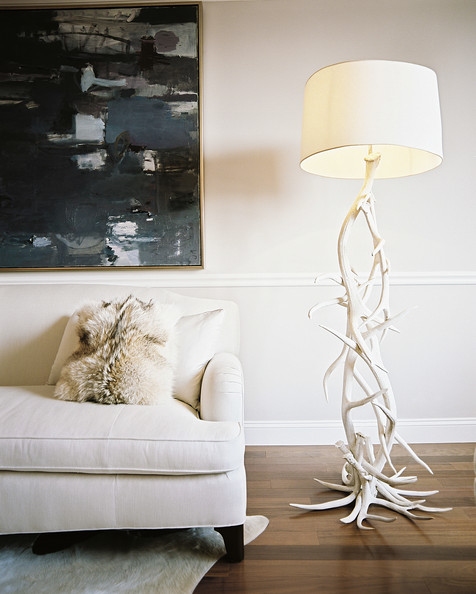 Fur Pillow - A floor lamp made of antlers beside a white couch