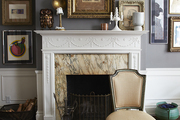 Large framed art above marble faced fireplace.