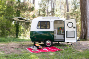 A green and white camper in the woods.