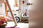 Window-lit kids room with wood bunk bed and contemporary furniture.