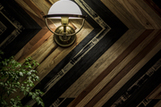 Vintage sconce on patterned natural wood wall.