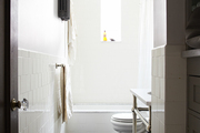 White tiled walls and small black tiled floors in window lit bathroom.