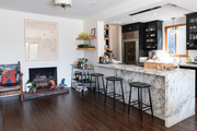 A kitchen with wooden floors and marble tile, complimented by pastel colored decor.