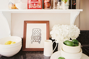 A Hugo Guinness print sits below a spice rack, next to hydrangeas on a black marble counter.
