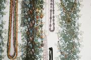 Necklaces hung from walls covered in floral wallpaper