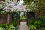 A shingled gate leading to a private garden space