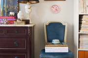 A wooden chest and a blue chair beside a white bookcase