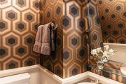 A contemporary bathroom with brown wallpaper.