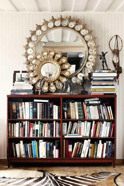 Gold Bookshelf - Two round mirrors above a bookcase and a zebra-hide rug