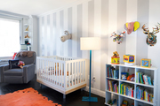 Small bookshelf with a matching white crib and rocking chair.