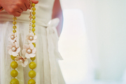 A Kate Spade New York beaded floral necklace is held by Deborah Lloyd, in a white linen dress.