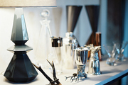 A collection of barware and a gray lamp on a white surface