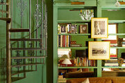 A green library and living room with built-in mirrored bookcases and a spiral staircase in a historic New Orleans home