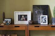 Framed artworks upon a pair of wood tables atop a tile floor