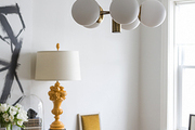 An unusual globe lighting fixture over a round dining table and wire chairs