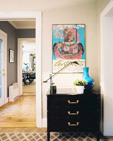Hallway Beige - A black chest topped with a blue vase, a potted plant, and a task lamp