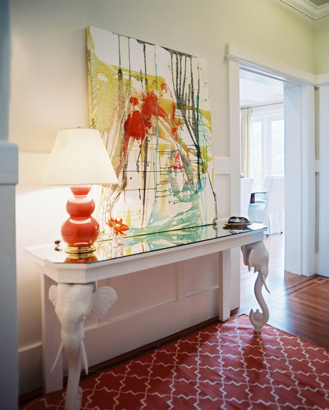 Hallway Green - An orange lamp and patterned rug balanced by a white elephant-motif console table