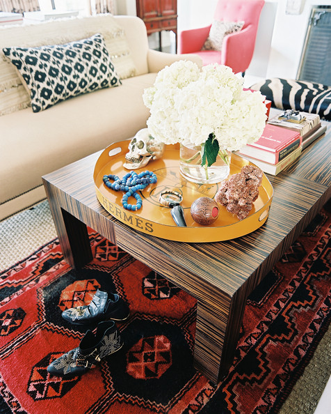 Hermes - Layered rugs beneath a rectangular coffee table topped with an Hermes tray