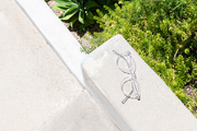 Clear-framed glasses sit on a cement curb.